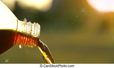 Cola flows from a plastic bottle against a background of...