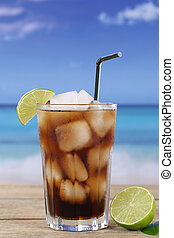 Cola in glass with lime on the beach