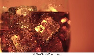 Cola in the glass with Ice cubes and bubbles rotating. Food...