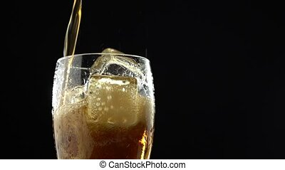 Cola is poured into a glass from a bottle. Black background...