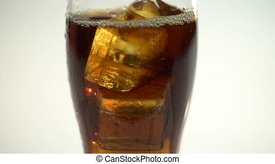 Cola is poured into a glass from a bottle. White background....