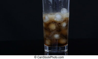 Cola is poured into a large long glass cup with pieces of ice inside on a black background.