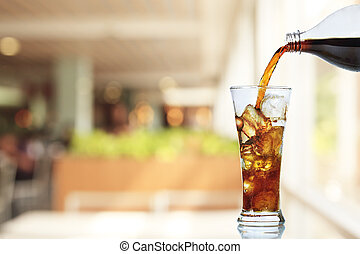 Cola is pouring into glass