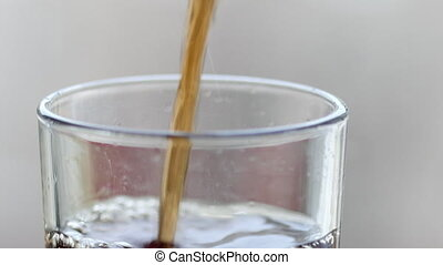 Cola is pouring into the glass with bubbles. UltraHD video -...