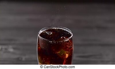 Cola pouring into glass with ice cubes. Close up - Cola...
