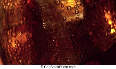 Cola pouring into the glass with Ice cubes and bubbles. Food...