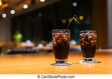 Cola with ice and straw in glass on the table.