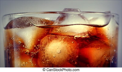 Cola with ice cubes background. Cola with Ice and bubbles in glass. Soda closeup. Food background. Stock full HD video footage 4K