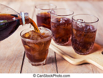 cola with ice cubes. - Cola drink is poured into a glass...