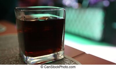 Cola with whiskey in large glass - night club, close up