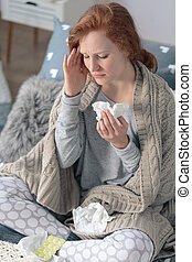 Cold and flu season, sick woman wrapped in a blanket holding her head suffering from sore throat and runny nose