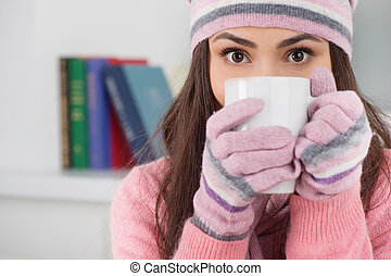 Cold and flue. Beautiful young woman in hat and gloves drinking tea while sitting at home
