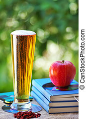 Cold beer and apple on books