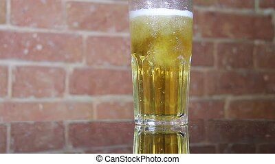 Cold beer from a dark bottle against a brick wall is poured into a large mug. High quality FullHD footage
