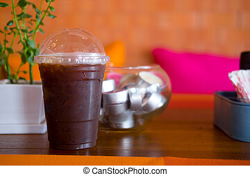 Cold black coffee with ice on wood table