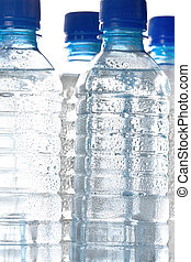 Clear unlabelled plastic bottles of healthy pure cold bottled water with water droplets on the exterior of the bottle
