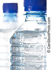 Cold bottled water - Clear unlabelled plastic bottles of...