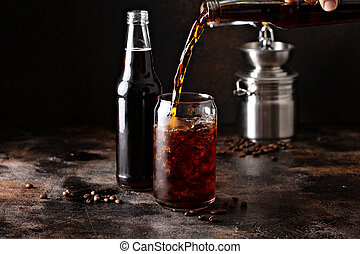 Cold brew iced coffee in glass bottles being poured over ice