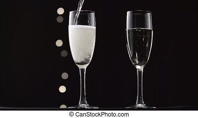 Cold champagne poured into two transparent glass of the...