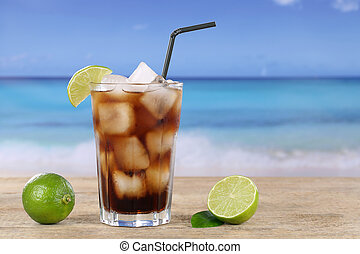 Cold cola in glass on the beach