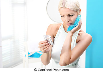 cold compress on the sore tooth. - The woman puts a cold...