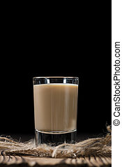 Glass with cold Cream Liqueur on vintage wooden background