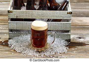 Cold dark beer in large glass mug with vintage crate with ice cold bottled beer on rustic wooden boards