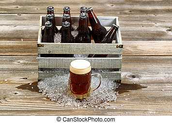 Cold dark beer with vintage crate filled with ice cold bottled beer on rustic wooden boards