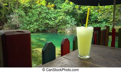 Cold drink near beautiful pond - Cold beverage standing at...