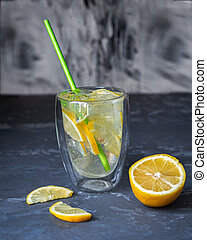 Cold drink with ice and lemon in a transparent thermo glass with cocktail tube