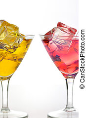 cold drinks - red and yellow drinks with ice cubes, close up