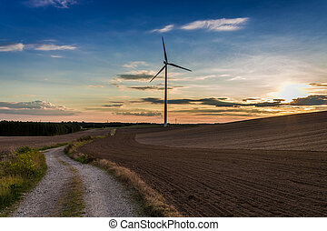Cold dusk at field with wind turbine in autumn
