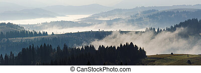 cold fog on hot sunrise in mountains - panorama of cold...