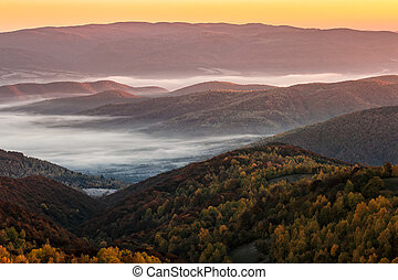 cold fog on hot sunrise in mountains - cold autumn morning...