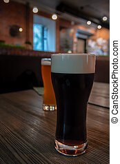 Cold Glass of dark kraft Beer standing on wooden table at a bar. Foam on the Stout beer. Pub in the background.