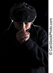 Cold hands - A man, dressed in Soviet attire, blowing in his...