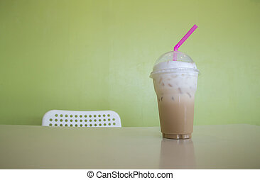 Cold ice coffee with cubes on wooden table in summer