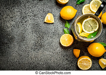 Cold lemonade in a jug with slices of lemon and green leaves.