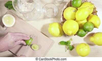 Cold lemonade in the decanter on the table - A man cuts lime...