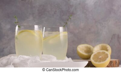 Cold lemonade or alcoholic cocktail with lemon, rosemary and...