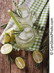Cold lemonade with lime, ice and rosemary close up in a glass jar on the table. vertical top view