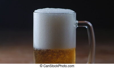 Cold Light Beer in a glass with black background, slow motion