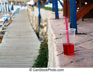 Cold red drink with straw at the beach