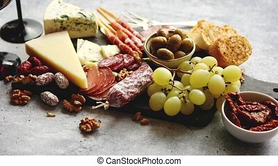 Cold snacks board with meats, grapes, wine, various kinds of...