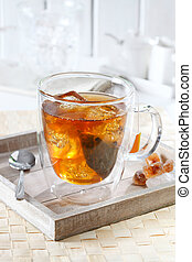 Cold tea with ice cubes on a tray