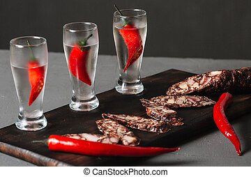 Cold vodka in a shot glass served with salami on a wooden cutting board on dark background