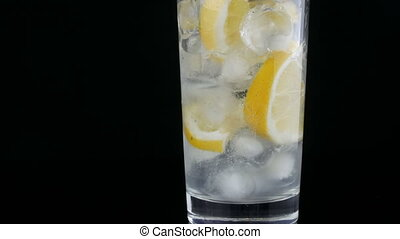 Cold water is poured into a transparent long glass with lemon slices and ice cubes on a black background.