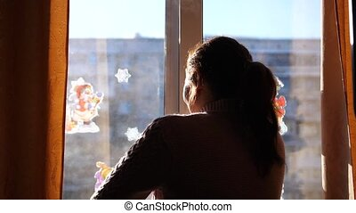 Cold winter day. The girl opens the window and breathes in...