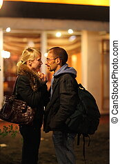 coldly fall nightly street. man and woman is staying near restaurant. people in focus.