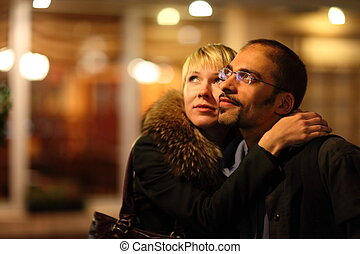 coldly nightly street. woman is emracing her man. focus on man's face.